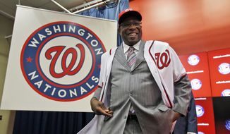 Dusty Baker smiles as he wears his new jersey and hat, during a news conference to present Baker as the new manager of the Washington Nationals baseball team, Thursday, Nov. 5, 2015, in Washington. (AP Photo/Alex Brandon)