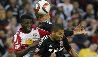 New York Red Bulls defender Kemar Lawrence, left, D.C. United forward Conor Doyle and Alvaro Saborio (9), right, head the ball during the second half of an MLS playoff soccer match, at RFK Stadium, Sunday, Nov. 1, 2015, in Washington. New York won 1-0. (AP Photo/Alex Brandon)