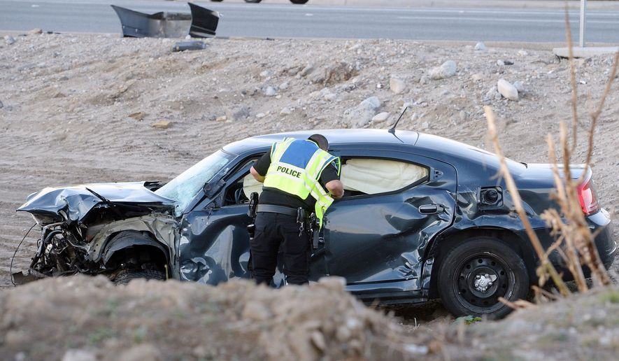 An Ontario police officer looks over the smashed vehicle which broadsided a San Bernardino Police department squad car killing officer Bryce Hanes early Thursday morning, Nov. 5, 2015 in Ontario, Calif. Officer Hanes was killed at the intersection of Etiwanda Avenue and Fourth Street early Thursday morning after his car was broad sided by a suspected drunk driver who ran a red light at an intersection, officials said.  (Will Lester/Inland Valley Daily Bulletin via AP)