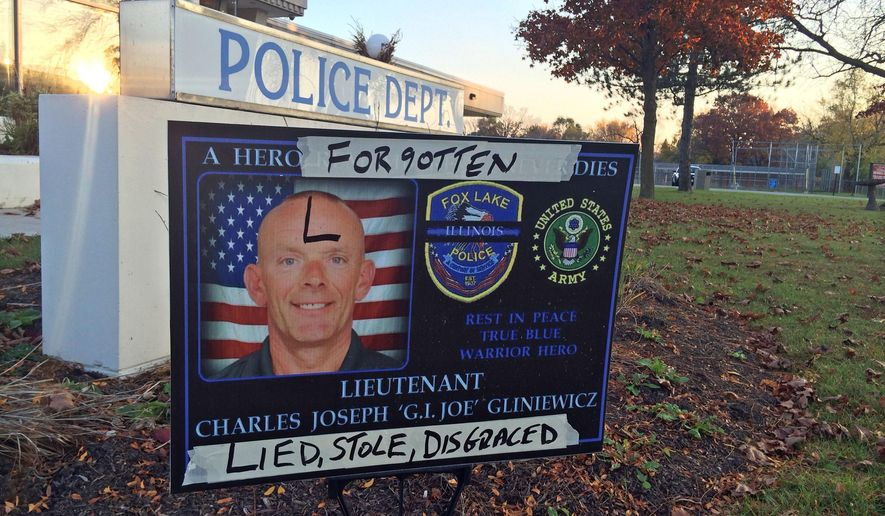 In this photo Wednesday, Nov. 4, 2015, a sign honoring Fox Lake Police Lt. Charles Joseph Gliniewicz is defaced outside Fox Lake Police Department in Fox Lake, Ill. Lake County officials confirmed Wednesday that Gliniewicz, 52, died Sept. 1 of a self-inflicted gunshot wound. Officials said Gliniewicz carefully staged his death to make it look like he was killed in the line of duty and had been stealing for years from a youth program he oversaw. (Lauren Zumbach/Chicago Tribune via AP) MANDATORY CREDIT, CHICAGO SUN-TIMES OUT, DAILY HERALD OUT, NORTHWEST HERALD OUT, DAILY CHRONICLE OUT, THE HERALD-NEWS OUT, THE TIMES OF NORTHWEST INDIANA OUT, TV OUT, MAGS OUT, NO SALES