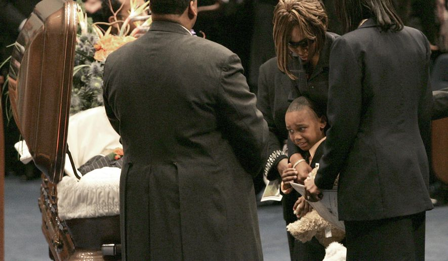 FILE - In this Jan. 6, 2007, file photo, Tierria Leonard, girlfriend of slain Denver Broncos cornerback Darrent Williams, and their son, Darius, 7, view the casket at Williams' funeral service for in Fort Worth, Texas. Williams was fatally shot in Denver. Darius Williams wonders all the time how his life would be different. He knows it would be. His father was a millionaire by 23 and an NFL starter on the Broncos. But what Darius wonders and what he lives with are two different things. Now 16 and a junior cornerback at Fort Worth Arlington Heights, he is trying to chase what Darrent achieved while living with only a memory. (Tom Pennington/Fort Worth Star-Telegram via AP, Pool)