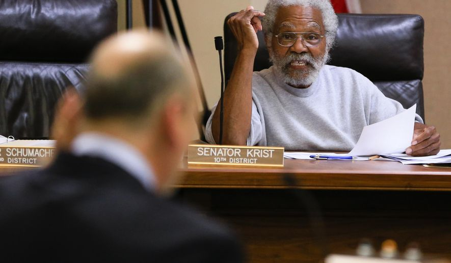 State Sen. Ernie Chambers of Omaha, right, puts a question to Scott Frakes, director of the Nebraska Department of Corrections, Thursday, Nov. 5, 2015, in Lincoln, Neb., during a legislative oversight committee that is looking into various problems in the state prison system. (AP Photo/Nati Harnik)