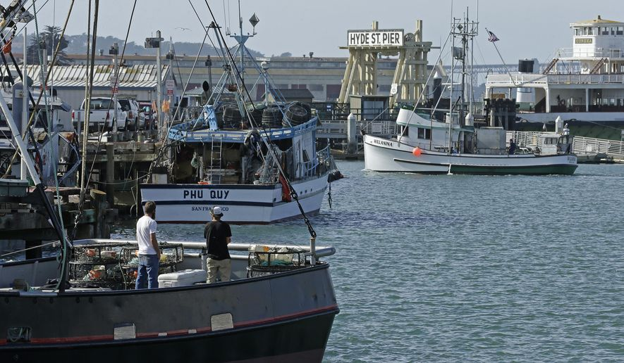 Fishermen stand on a boat loaded with crab pots, left, Thursday, Nov. 5, 2015, at Fisherman's Wharf in San Francisco. Wildlife authorities delayed the Dungeness crab season and closed the rock crab fishery for most of California on Thursday, just days after warning of dangerous levels of a neurotoxin linked to a massive algae bloom off the West Coast. (AP Photo/Ben Margot)