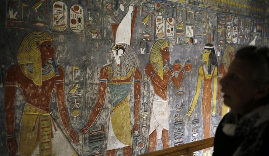 A visitor looks at colored carvings on a wall at the Horemheb tomb, the last pharaoh of the 18th Dynasty of Egypt, in the Valley of the Kings in Luxor, Egypt, Thursday, Nov. 5, 2015. Egypt has opened three tombs in the ancient city of Luxor to the public, hoping to spur tourism interest despite the shadow of last weekend's airline crash in the Sinai Peninsula. (AP Photo/Amr Nabil)