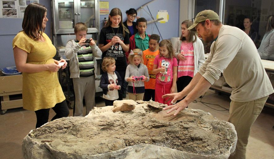 Tom Suazo, right, a fossil predator with the New Mexico Museum of Natural History and Science, tells a group of children about the museum's latest find as discover Amanda Cantrell, left, listens during a public unveiling in Albuquerque, N.M., on Thursday, Nov. 5, 2015. The baby Pentaceratops skull on display in the museum's preparation room is the first to ever be discovered. (AP Photo/Susan Montoya Bryan)