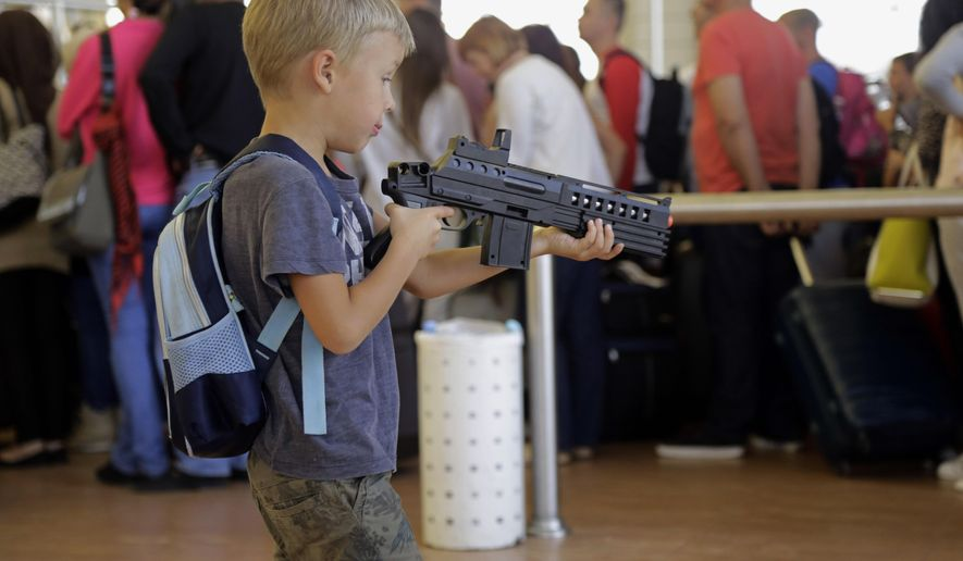 A child plays with a toy gun in the departure area before boarding a flight from Sharm el-Sheikh, south Sinai, Egypt, Friday, Nov. 6, 2015. Egyptian police carried out detailed security checks on Friday at the airport in Sharm el-Sheikh, the resort from where the doomed Russian plane took off last weekend, after U.K. officials confirmed that flights will start bringing stranded British tourists home from the Sinai Peninsula. (AP Photo/Thomas Hartwell)