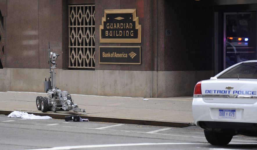 A remote-controlled robot examines a suspicious package outside the Guardian building in Detroit on Friday, Nov. 6, 2015. The building was evacuated as authorities investigated the scene. The building reopened just after noon. (David Coates/The Detroit News via AP)