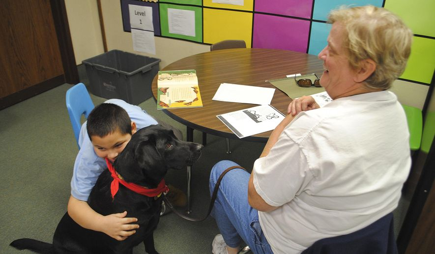 In this Monday, Nov. 2, 2015 photo, Beardsley Elementary student Juan-Oscar Rodriguez Tilley, left, hugs volunteer Lou Putnam's therapy dog, Birdie, during a mentoring session in Elkhart, Ind. The school has a new 30-30-30 program to help English language learners, in which 30 mentors pair with 30 students and work with them for 30 minutes each week. (Michelle Sokol/The Elkhart Truth via AP)
