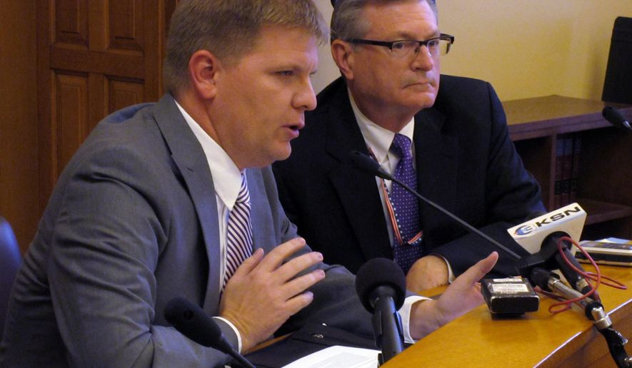 Shawn Sullivan, left, Kansas Gov. Sam Brownback's budget director, answers questions from reporters about adjustments to the state's budget to avert a deficit following a new, more pessimistic forecast for revenue collections, Friday, Nov. 6, 2015, at the Statehouse in Topeka, Kan. Watching to his right is Raney Gilliland, director of the Kansas Legislative Research Department. (AP Photo/John Hanna)