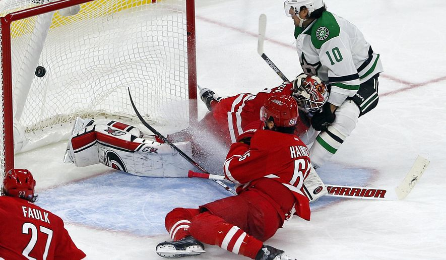 Dallas Stars' Patrick Sharp (10) crashes into Carolina Hurricanes goalie Eddie Lack (31) after beating Ron Hainsey (65) down the ice to score the go-ahead goal during the third period of an NHL hockey game, Friday, Nov. 6, 2015, in Raleigh, N.C. (AP Photo/Karl B DeBlaker)