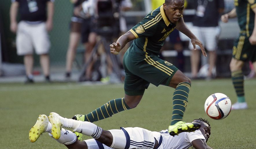 FILE - In this July 18, 2015, file photo, Portland Timbers forward Darlington Nagbe, top, leaps over Vancouver Whitecaps midfielder Gershon Koffie as he chases the ball during the first half of an MLS soccer game in Portland, Ore. Portland Timbers midfielder Darlington Nagbe has been picked for the U.S. national team, less than two months after becoming an American citizen. New York Red Bulls defender Matt Miazga also was on the 23-man roster announced Friday, Nov. 6, 2015,  and could make his national team debut in World Cup qualifiers against St. Vincent and the Grenadines at St. Louis on Nov. 13 or at Trinidad and Tobago four days later. (AP Photo/Don Ryan, File)
