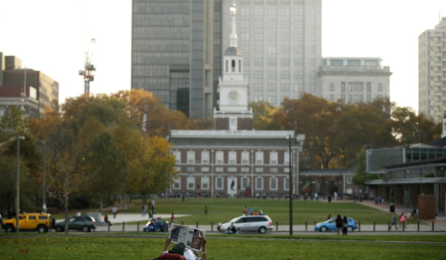 A man reads a newspaper near Independence Hall, Friday, Nov. 6, 2015, in Philadelphia. America's birthplace has been named the country's first World Heritage City. The Organization of World Heritage Cities voted in Peru on Friday to add Philadelphia. The city qualifies because Independence Hall is a UNESCO World Heritage Site. (AP Photo/Matt Slocum)