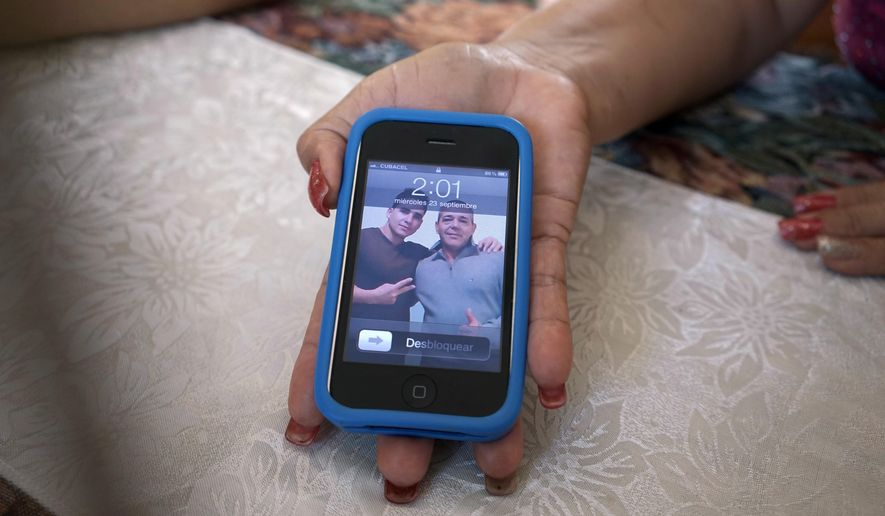 In this Sept. 23, 2015 photo, Olea Lastre, a hairdresser, shows a photo of her husband Antonio Cardenas with her son Jose Fuentes Lastre, taken in the U.S. after they survived 10 days at sea on a raft in the Florida Straits, on her cell phone in Camaguey, Cuba. The men fled last year and now live in Portland, Oregon, where they were resettled by a charity and her husband works in a meatpacking factory.  (AP Photo/Christine Armario)