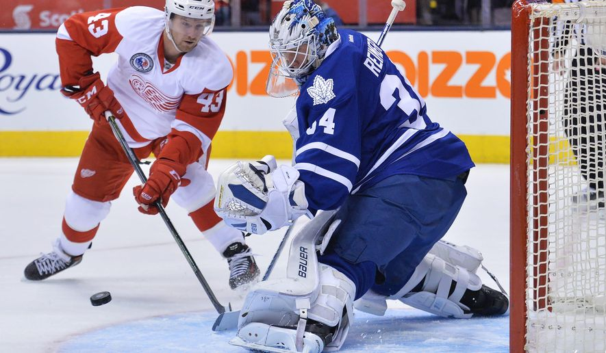 Toronto Maple Leafs' goalie James Reimer (34) makes a save against Detroit Red Wings' forward Darren Helm (43) during first-period NHL hockey game action in Toronto, Friday, Nov. 6, 2015. (Nathan Denette/The Canadian Press via AP) MANDATORY CREDIT