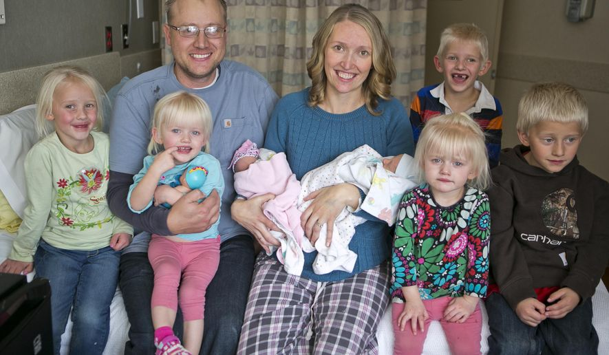 Tiffany and Chris Goodwin of Three Forks, Mont., pose for a family photo with their children, from left, Eliza, Brielle, Olivia, Carter, Mason, Emalynn and Josh on Wednesday, Nov. 4, 2015 at the Bozeman Health Deaconess Hospital in Bozeman, Mont. Tiffany gave birth to her third set of twins, Olivia and Carter, on Monday. (AP Photo/Bozeman Daily Chronicle, Adrian Sanchez-Gonzalez)