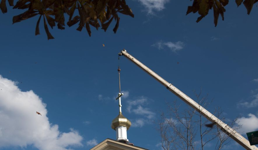 One of three gold onion domes and crosses is installed on top of St George Byzantine Catholic Church, Thursday, Nov. 5. 2015, in Bay City, Mich.  The Rev. David A. Hannes says the three domes are similar in style to those found atop churches in Ukraine and Russia, are more than just an ornate topping at the church.    (Nicole Hester/The Bay City Times via AP) LOCAL TELEVISION OUT; LOCAL INTERNET OUT; MANDATORY CREDIT