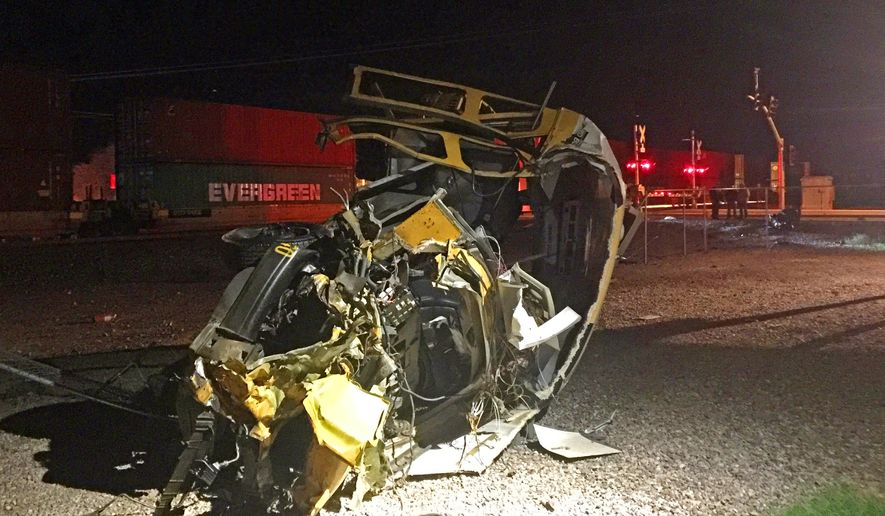 This photo taken Thursday, Nov. 5, 2015 and provided by the Maricopa, Ariz., Police Department shows a damaged school bus after it stalled on a grade crossing and was struck by a freight train in Maricopa. The driver, the only occupant, safely got off the bus before it was struck. The bus driver and the train's crew were emotionally shaken but physically uninjured. (Ricardo Alvarado/Maricopa Police Department via AP)