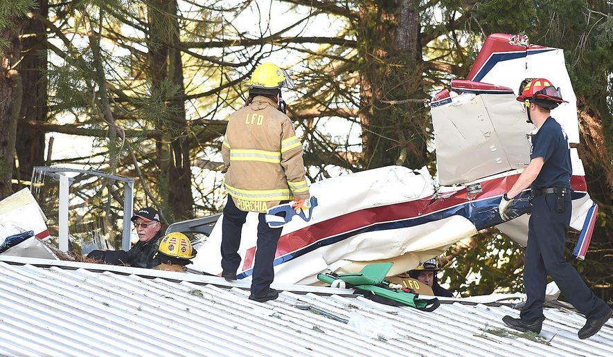 Pilot Marion Knox, left, waits in the cockpit of his plane as Albany and Lebanon firefighters work to free him after he clipped a tree and crashed onto the roof of a shop near Lebanon, Ore., Friday Nov. 6, 2015. Both Knox and his passenger, Steve Edmiston were injured in the crash.  (Mark Ylen/Albany Democrat-Herald via AP) MANDATORY CREDIT
