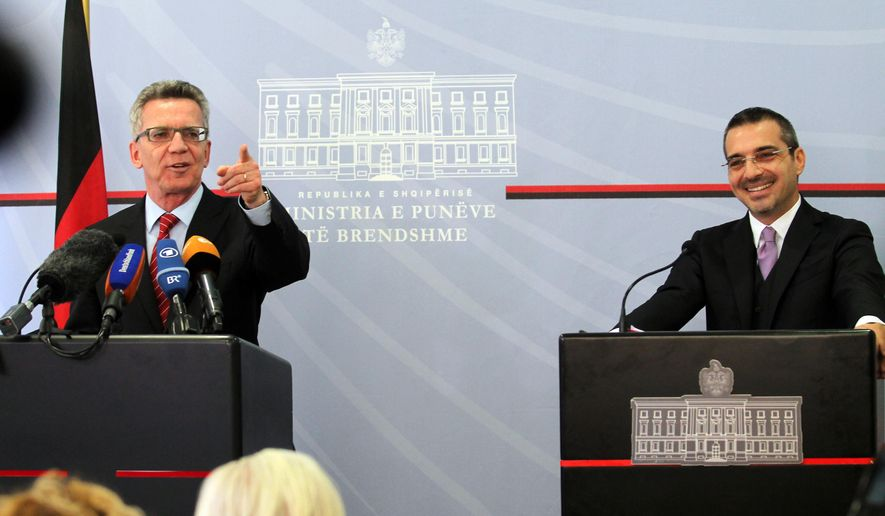 German Interior Minister Thomas de Maiziere, left,  speaks at a news conference after meeting with Albanian counterpart Saimir Tahiri, in Tirana, Albania, Friday, Nov. 6, 2015.  De Maiziere calls on Albanians to stop asking for political asylum in Germany as there is no ground for their claims. (AP Photo/Hektor Pustina)