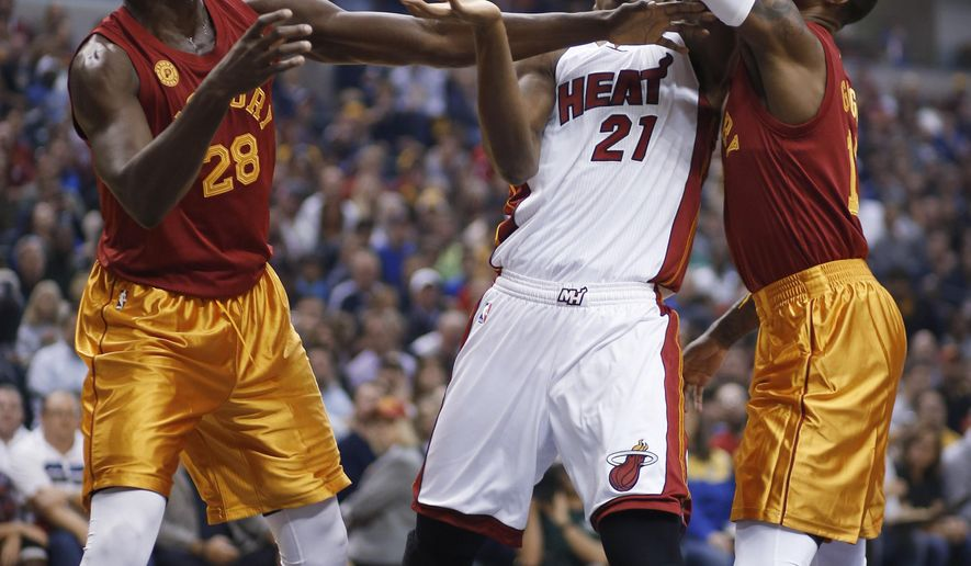 Miami Heat center Hassan Whiteside, center, goes for a rebound between Pacers defenders Ian Mahinmi, left, and Paul George during the first half of an NBA basketball game in Indianapolis, Friday, Nov. 6, 2015. (AP Photo/AJ Mast)