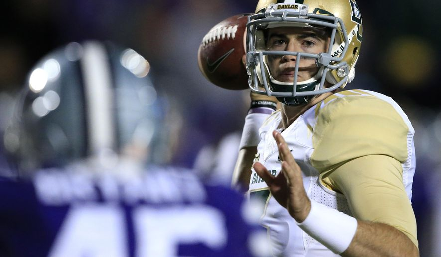 Baylor quarterback Jarrett Stidham, right, passes to a teammate over Kansas State defensive end Marquel Bryant (45) during the second half of an NCAA college football game in Manhattan, Kan., Thursday, Nov. 5, 2015. Baylor defeated Kansas State 31-24. (AP Photo/Orlin Wagner)
