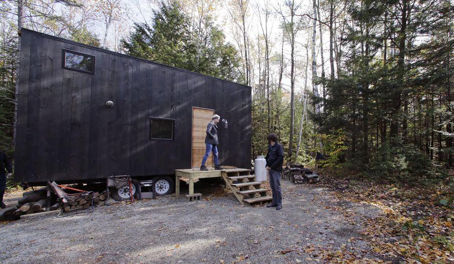 "In this Tuesday, Oct. 20, 2015 photo, Hilary Lentz, of Pittsburgh, Pa., and her husband Shane leave the tiny house which they rented for a weekend in Croydon, N.H. As the tiny house phenomenon sweeps the nation, Harvard's Millennial Housing Lab thinks a tryout is in order for people toying with radically downsizing their lives. Its new ""Getaway"" project gives the curious an opportunity to spend a night or two in one of three tiny houses and get a real feel for the lifestyle before taking the plunge. (AP Photo/Charles Krupa)"