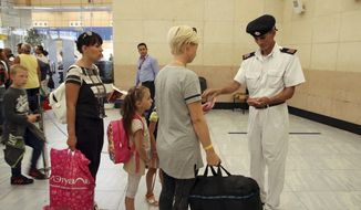 Tourists have their documents checked by Egyptian police as they prepare to be evacuated from Sharm el-Sheikh airport, south Sinai, Egypt, Friday, Nov. 6, 2015. (AP Photo/ Vinciane Jacquet)