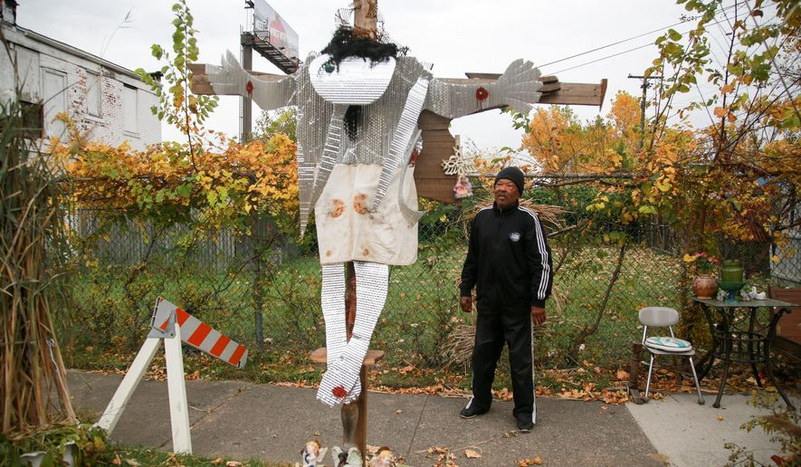"""ADVANCE FOR THE WEEKEND OF NOV. 7-8 AND THEREAFTER - In a Wednesday, Oct. 22, 2015 photo, Pete Jackson, 77, of Belleville stands next to his latest artpiece, """"The Old Rugged Cross"""" that stands next to his family home in Highland Park, Mich. like a scarecrow. The sign on the lawn says there's a yard sale today. But there's been a sale here every day forever. (Kimberly P. Mitchell/Detroit Free Press via AP)  DETROIT NEWS OUT; TV OUT; MAGS OUT; NO SALES; MANDATORY CREDIT DETROIT FREE PRESS"""