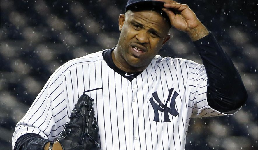 """FILE - In this Oct. 1, 2015, file photo, New York Yankees starting pitcher CC Sabathia (52) struggles with his cap in the rain during the first inning of a baseball game against the Boston Red Sox in New York. Sabathia says he had """"no other option"""" than to leave the team for treatment for alcoholism ahead of its loss to Houston in the one-game AL wild-card playoff. (AP Photo/Kathy Willens, File)"""