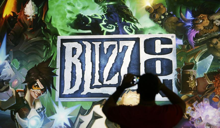 "A man takes pictures of the BlizzCon sign at the opening ceremony of the convention, Friday, Nov. 6, 2015, in Anaheim, Calif. ""World of Warcraft"" maker Blizzard is hosting its ninth annual fan-centric convention opening Friday. (AP Photo/Jae C. Hong)"