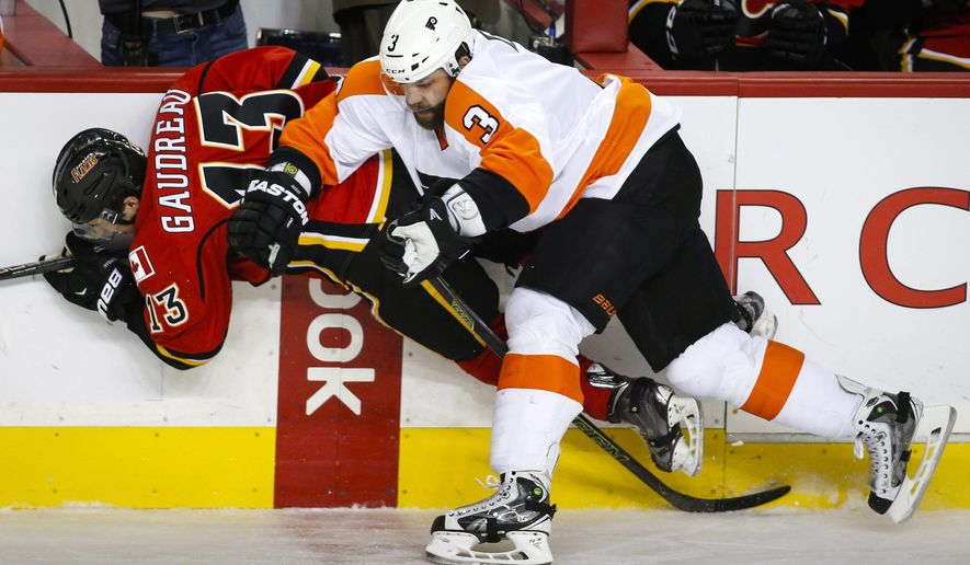 Philadelphia Flyers' Radko Gudas, right, of the Czech Republic, checks Calgary Flames' Johnny Gaudreau during second-period NHL hockey game action in Calgary, Alberta, Thursday, Nov. 5, 2015. (Jeff McIntosh/The Canadian Press via AP) MANDATORY CREDIT
