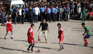 Former soccer player David Beckham plays football with Nepalese students in Bhaktapur, Nepal, Friday, Nov. 6, 2015. Beckham, who is in Nepal filming a documentary for UNICEF, visited the Shree Padma Higher Secondary School, where classes are being held in temporary sheds. He later played soccer with the children at an open courtyard, cheered on by hundreds of fans. (AP Photo/Niranjan Shrestha)
