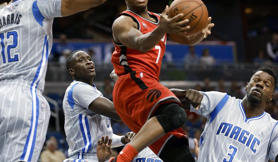 Toronto Raptors guard Kyle Lowry (7) goes up for a shot between Orlando Magic forward Tobias Harris (12) and center Dewayne Dedmon (3) during the first half of an NBA basketball game Friday, Nov. 6, 2015, in Orlando, Fla. (AP Photo/John Raoux)