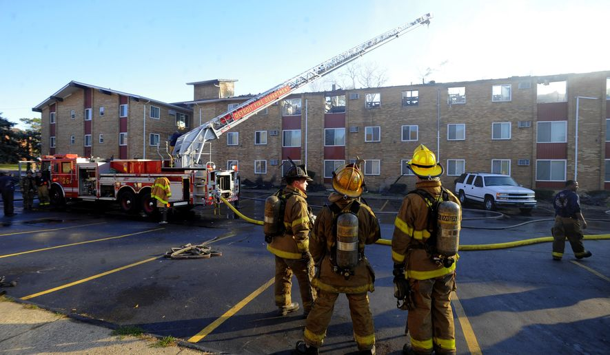 Detroit Firefighters battle a three-alarm fire, Tuesday Nov. 3, 2015 in Detroit's west side.  A woman has apologized for the massive fire that she and authorities said was accidentally started by her efforts to eradicate bedbugs from her apartment.  (Steve Perez/Detroit News via AP)  DETROIT FREE PRESS OUT; HUFFINGTON POST OUT; MANDATORY CREDIT