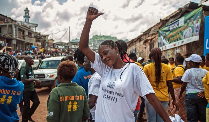 A woman celebrates with others as the country is declared Ebola free in the city of Freetown, Sierra Leone, Saturday, Nov. 7,  2015. The World Health Organization declared Sierra Leone free from Ebola transmissions on Saturday, as West Africa battles to stamp out the deadly virus that is holding on in neighboring Guinea.(AP Photo/Aurelie Marrier d'Unienvil)