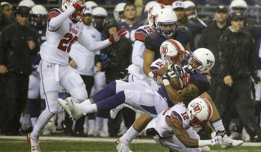 Washington's Dwayne Washington comes down on top of Utah defensive back Justin Thomas (12) as he is tackled by Utah's Chase Hansen (22) during the first half of an NCAA college football game, Saturday, Nov. 7, 2015, in Seattle. (AP Photo/Ted S. Warren)