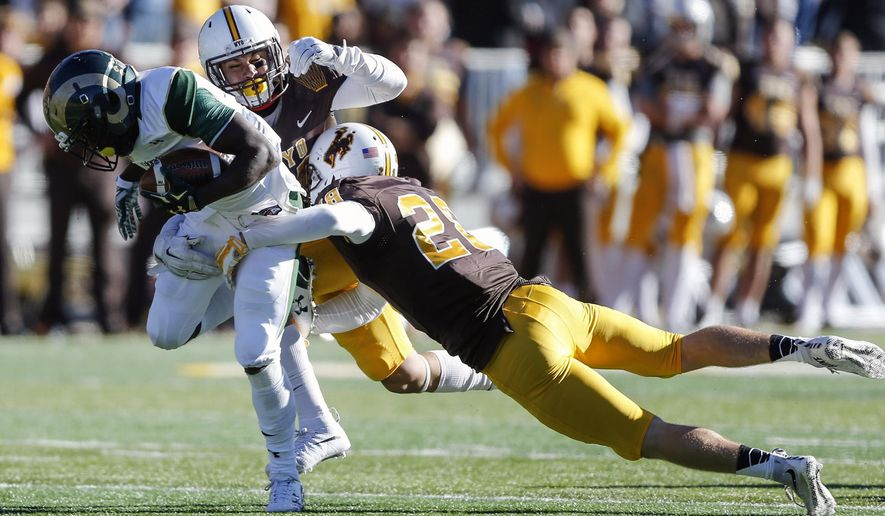 Wyoming's Marcus Epps, center, and Andrew Winged, right, try to tackle Colorado State's Dalyn Dawkins during the second quarter of an NCAA college football game, Saturday, Nov. 7, 2015, in Laramie, Wyo. (AP Photo/Michael Smith)