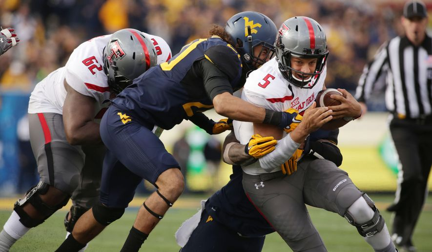 Texas Tech quarterback Patrick Mahomes (5) is tackled by West Virginia linebacker Edward Muldrow (20) during the second half of an NCAA college football game, Saturday, Nov. 7, 2015, in Morgantown, W.Va. West Virginia won 31-26. (AP Photo/Raymond Thompson)