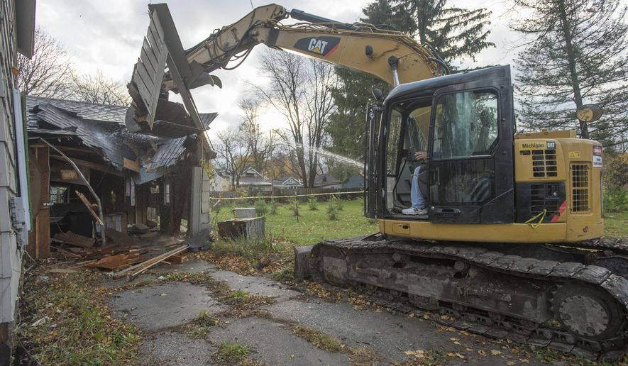 Saginaw Mayor Dennis Browning runs an excavator  to demolish the garage of the home where he raised his family in the 1970s and 80s on Friday, Nov. 6, 2015 in Saginaw, Mich.  The home is one of nearly 1,000 vacant, blighted homes in Saginaw being razed, funded by a federal grant.  (Jeff Schrier/The Saginaw News via AP) ALL LOCAL TELEVISION OUT; LOCAL TELEVISION INTERNET OUT; MANDATORY CREDIT