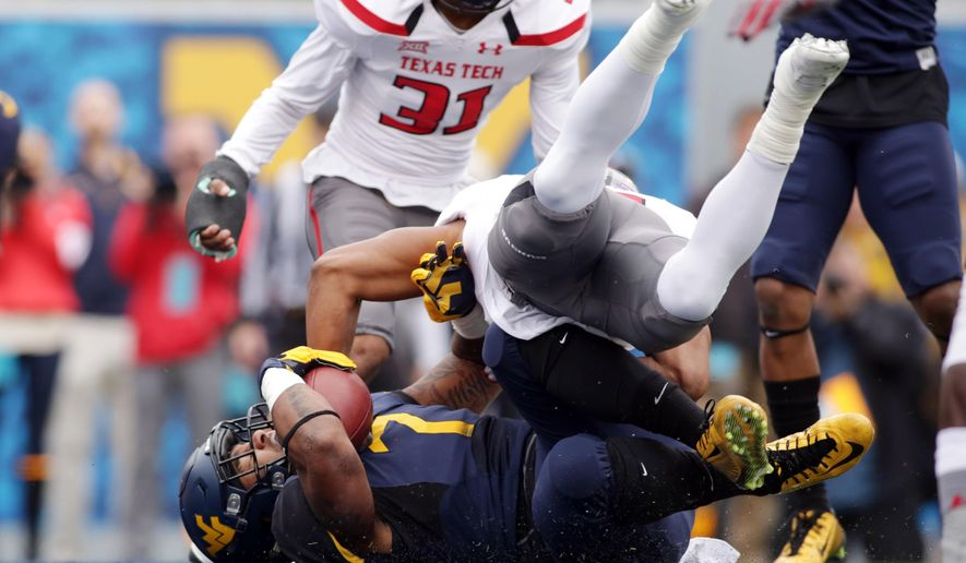 West Virginia running back Rushel Shell, bottom, powers through Texas Tech defensive back Keenon Ward (15) to score a touchdown during the first half of an NCAA college football game, Saturday, Nov. 7, 2015, in Morgantown, W.Va. (AP Photo/Raymond Thompson)