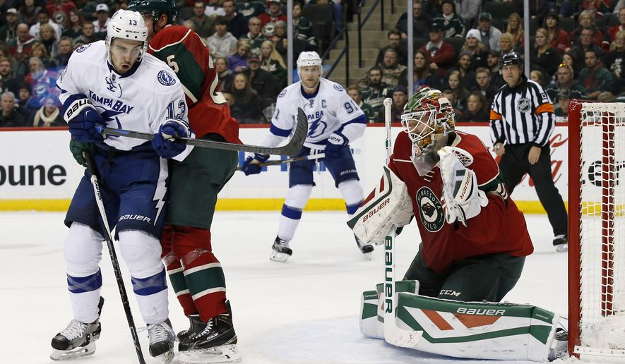 Minnesota Wild goalie Devan Dubnyk, front right, catches a shot in front of Tampa Bay Lightning center Cedric Paquette (13) and Wild defenseman Jonas Brodin, center, of Sweden, during the second period of an NHL hockey game in St. Paul, Minn., Saturday, Nov. 7, 2015. (AP Photo/Ann Heisenfelt)
