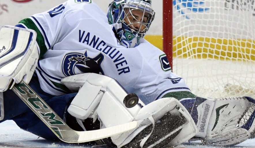Vancouver Canucks goaltender Ryan Miller makes a save during the first period of an NHL hockey game against the Buffalo Sabres, Saturday Nov. 7, 2015 in Buffalo, N.Y. (AP Photo/Gary Wiepert)