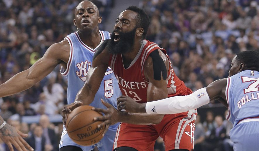 Houston Rockets guard James Harden, center, drives to the basket between Sacramento Kings' James Anderson, left and Darren Collison during the first quarter of an NBA basketball game in Sacramento, Calif., Friday, Nov. 6, 2015. (AP Photo/Rich Pedroncelli)