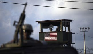 A U.S. trooper mans a machine gun in the turret on a vehicle as a guard looks out from a tower in front of the detention facility at Guantanamo Bay U.S. Naval Base, Cuba, in this March 30, 2010, file photo. (AP Photo/Brennan Linsley, File)