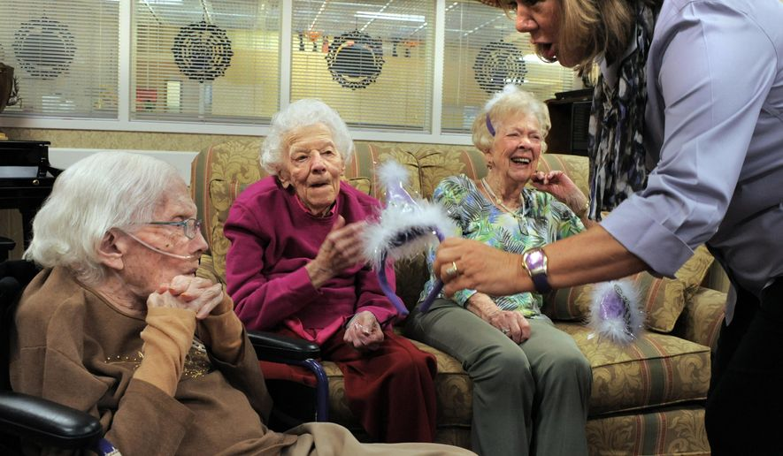 ADVANCE FOR THE WEEKEND OF NOV. 7-8 AND THEREAFTER - In a Thursday, Oct. 22, 2015 photo, from the left, Bea Risinger, Claribel Conway, and Alice Smart receive little hats from Connie Johnson to wear at a gathering at the Life Care Center nursing home in Colorado Springs, Colo. The three women all turn 103 this year within three weeks of each other, Bea, October 24, Alice, October 31 and Claribel, November 14. Connie Johnson is the general manager of the Bridge Assisted Living. (Carol Lawrence/The Gazette via AP)