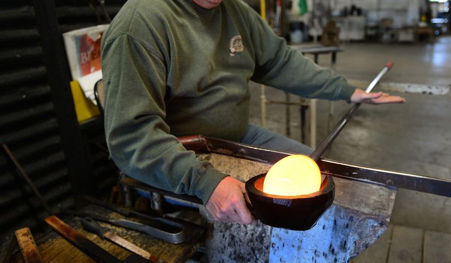 ADVANCE FOR SUNDAY NOV 8 AND THEREAFTER This Thursday Oct. 29, 2015 photo shows Perry Bays shapes the molten glass with a wooden mold in the beginning process of making the water droplet at Blenko Glass Company, in Milton, W. Va.  Barrie Kaufman is partnering with the company on a special collaborative project focusing on clean water and sustainability. (Kenny Kemp/Charleston Gazette-Mail via AP)