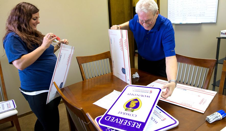 "ADVANCE FOR SATURDAY, NOV. 7, 2015 - In this photo taken on Wednesday, Nov. 4, 2015, Ashlie Congdon, left, and Ron Julianelle place ""Reserved Combat Wounded"" signs in packages before shipping them at Wounded Warrior Family Support, in Omaha, Neb. (Megan Farmer/Omaha World-Herald via AP) MAGS OUT; ALL NEBRASKA LOCAL BROADCAST TELEVISION OUT; MANDATORY CREDIT"