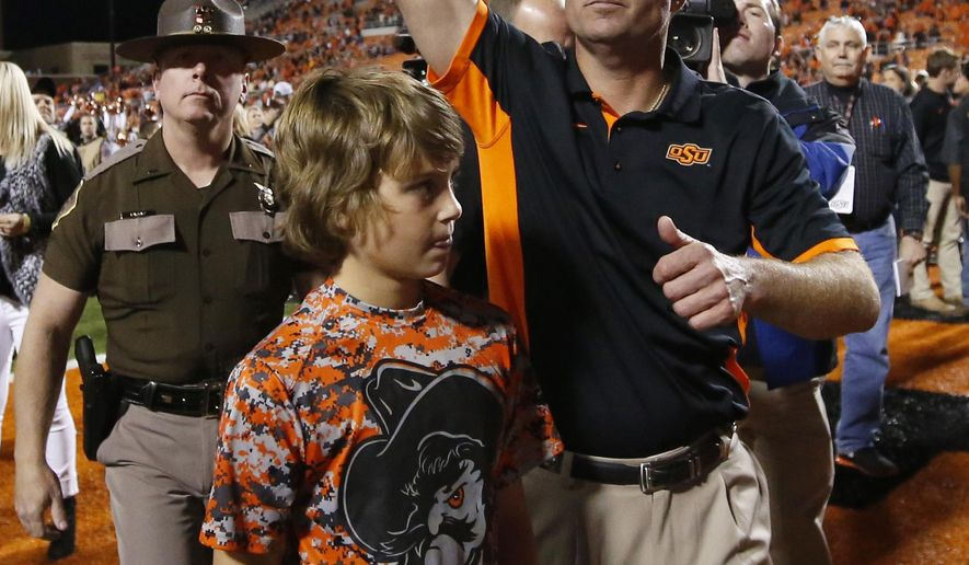 Oklahoma State head coach Mike Gundy, right, gestures to fans as he walks off the field with his son Gage Gundy, left, following a victory over TCU in an NCAA college football game in Stillwater, Okla., Saturday, Nov. 7, 2015. Oklahoma State won 49-29. (AP Photo/Sue Ogrocki)