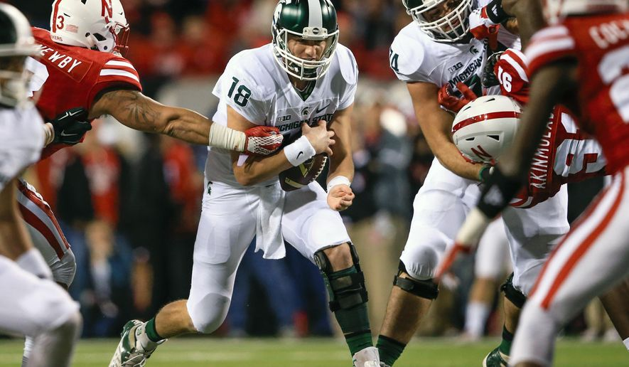 Michigan State quarterback Connor Cook (18) runs past Nebraska linebacker Marcus Newby during the first half of an NCAA college football game in Lincoln, Neb., Saturday, Nov. 7, 2015. (AP Photo/Nati Harnik)