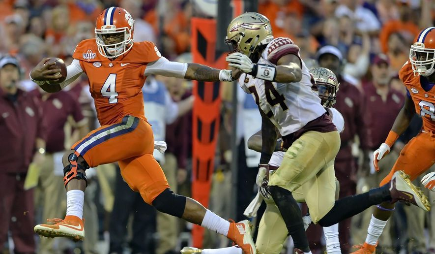 Clemson quarterback Deshaun Watson (4) fends off Florida State's Terrance Smith to gain a first down during the first half of an NCAA college football game Saturday, Nov. 7, 2015,  in Clemson,  S.C.  (AP Photo/Richard Shiro)